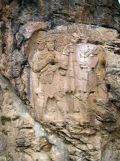 giant god Adad & mixed-breed king carved into rock, keeping the scene for thousands of years